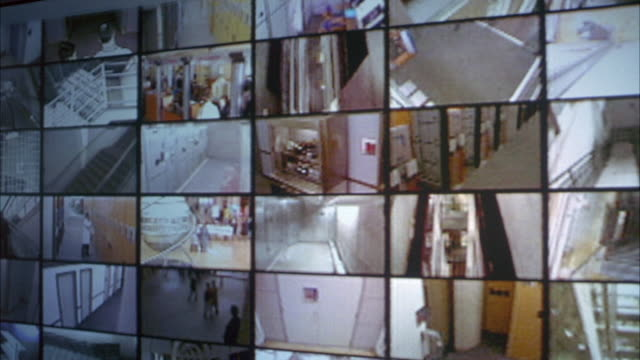 MEDIUM ANGLE OF A BANK OF TV OR TELEVISION  SECURITY MONITORS. MONITORS DISPLAY ACTIVITIES CAPTURED BY SURVEILLANCE CAMERAS. COULD BE SECURITY ROOM INSIDE SHOPPING MALL OR HOTEL. MONITORS SHOW ACTIVITIES IN STAIRWELLS AND HALLWAYS AND OPEN AREA WITH REVOL