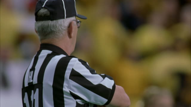 STEADICAM OF ON FIELD ACTIVITIES AT FOOTBALL GAME. SEE REFEREE WEARING GLASSES IN BLACK AND WHITE STRIPED JERSEY, CAMERAMAN WITH REPORTER, FOOTBALL OFFICIAL HOLDING BALL MARKER, AND CHEERLEADERS WITH GOLD POM POMS. OUT OF FOCUS IMAGES OF SPECTATORS IN BAC