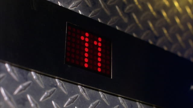 "close angle, up angle of digital elevator floor display. display reads in red lights the number ""7"" and counts up to ""30"", skipping the number ""13"". see industrial metal surface behind timer and flashes of yellow light from off camera source. could be use - lift stock videos & royalty-free footage"
