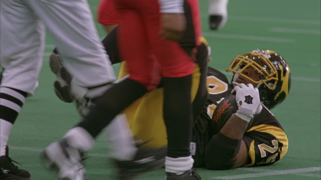 HAND HELD OF FOOTBALL GAME. CAMERA PANS TO DIFFERENT CORNERS OF GAME FIELD. SEE FOOTBALL PLAYERS. SEE PLAYERS JUMPING AND ENERGIZED. FOOTBALL TEAM UNIFORM COLORS ARE RED VERSUS YELLOW. SEE FOOTBALL TEAM PLAYER TACKLE OTHER PLAYER.