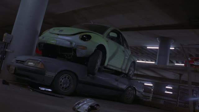 medium angle of parking garage or covered parking lot. see white fluorescent lights on ceilings of levels. see dirty or rusty blue 5.0 1987 ford mustang parked head first in garage with  lime green volkswagen new beetle stacked on top. see both cars broke - volkswagen stock-videos und b-roll-filmmaterial