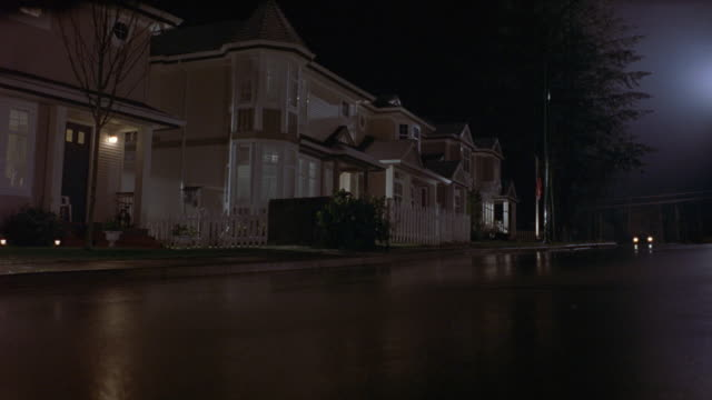 up angle of residential neighborhood. see empty streets in front of tract housing. two-story houses are beige with turrets and pitched roofs. lights are on in front porches. 1950's era vintage care, red 1957 cadillac, with headlights on drives toward came - wet wet wet stock videos & royalty-free footage