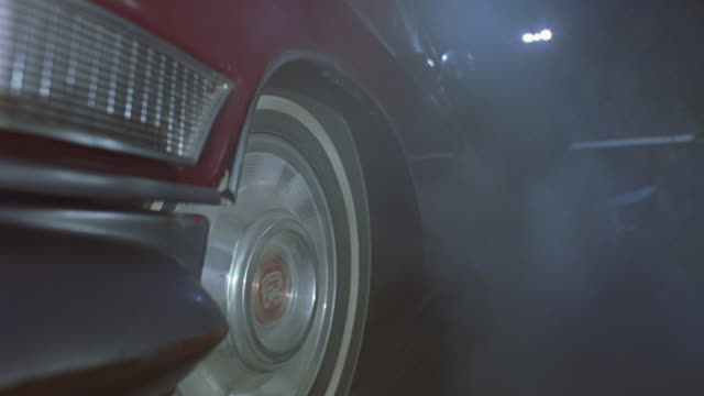 vídeos de stock, filmes e b-roll de up angle of street as red cadillac car drives down road. camera from side of car in front of driver's side front wheel. see car driving backwards, with smoke or dust clouds form. see car stop and drive forward towards camera. - cadillac