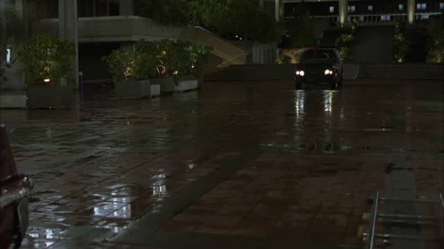 vídeos de stock, filmes e b-roll de tracking shot of black 1999 cadillac suv driving down paved courtyard to rear end 1957 red cadillac series 62. see potted plants, trees, bushes, stairs, and building walk ways in background. car crash, collision. - cadillac