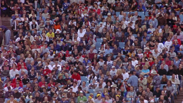 wide angle of sports arena stands, crowds.  stadium spectators cheering, watching sports. could be baseball, football, hockey, basketball. crowd gets excited, as if a team has scored. - wide angle stock videos & royalty-free footage
