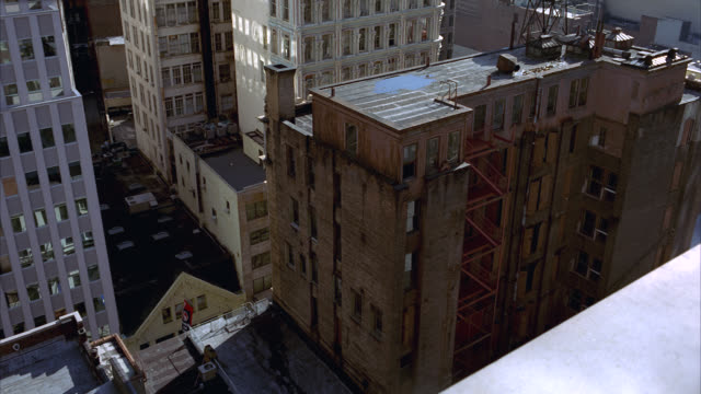 high angle down of a new york lower class apartment building. rooftops, fire escape visible. - fire escape stock videos & royalty-free footage