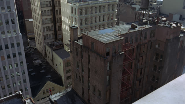 high angle down of midtown manhattan in new york city high rises, apartment buildings and skyscrapers. sunny day with blue skies. - fire escape stock videos & royalty-free footage