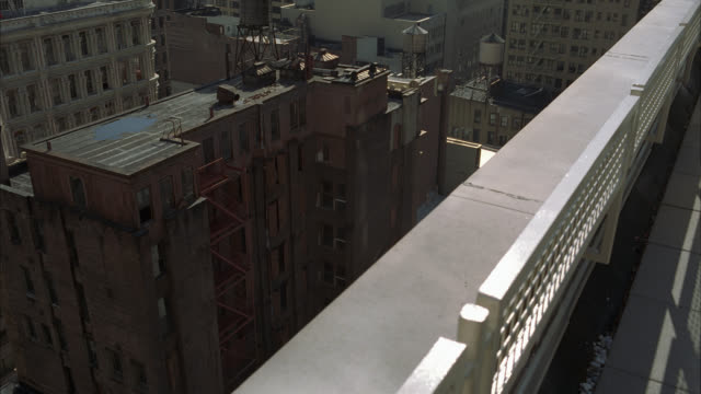 high angle down from a rooftop, railing, of a new york lower class apartment building. fire escape visible. - fire escape stock videos & royalty-free footage