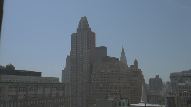 wide angle of roofs or rooftops of city skyline. high rises and skyscrapers. could be apartment or office buildings. metlife tower in bg. windows. water tank or tower on roof of building in fg. church steeple visible. - steeple stock videos & royalty-free footage