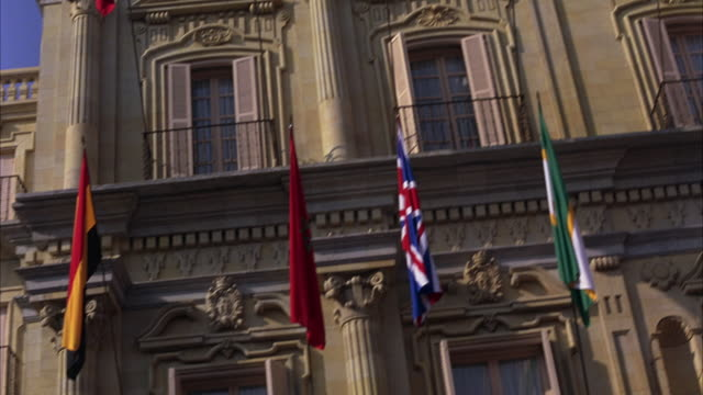 hand held of various european flags hanging off second-story balconies of replica plaza mayor from salamanca. renaissance architecture. carvings and corinthian columns. government or municipal building and tourist site. - korinthisch stock-videos und b-roll-filmmaterial