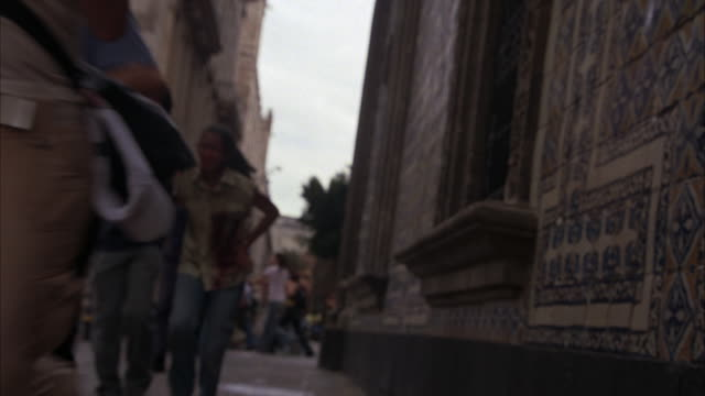 HAND HELD OF PEOPLE TURNING CORNER ONTO SIDE STREET IN EUROPE OR MEXICO CITY AND RUNNING. STONE RENAISSANCE BUILDINGS. COULD BE PANIC REACTION TO DISASTER OR OTHER EVENT. WOMAN CLUTCHING HIP WITH BLOOD OR DIRT ON HER SHIRT. INJURED OR WOUNDED FROM GUNFIRE