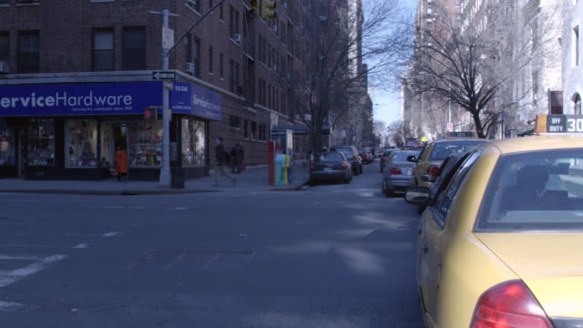 wide angle of nyc street. cars and taxis in traffic. one way street sign, buildings. hardware store on corner. pedestrians. gridlock. - one way stock videos & royalty-free footage