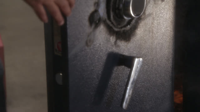 medium angle of safe with burn marks on it. lock has been picked using welding torch. mans arm appears with screwdriver or other tool. - 金庫点の映像素材/bロール