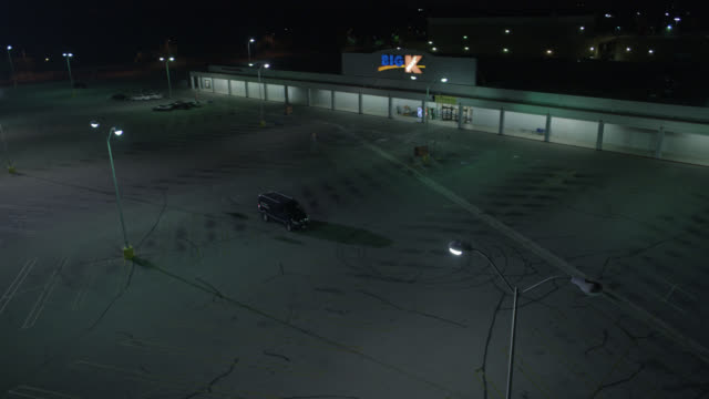 """vídeos de stock e filmes b-roll de high angle down of empty parking lot at """"big k"""" or kmart. street lamps and skid marks. car drives up to parked van, waits, van drives away. headlights are on. - parking"""