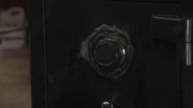 medium angle of safe with burn marks on it. lock has been picked using welding torch. could be robbery. - 金庫点の映像素材/bロール