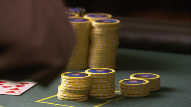 close angle of a stack of chips on a green felt gambling table.  the dealer puts down the cards for blackjack. - hand of cards stock videos & royalty-free footage