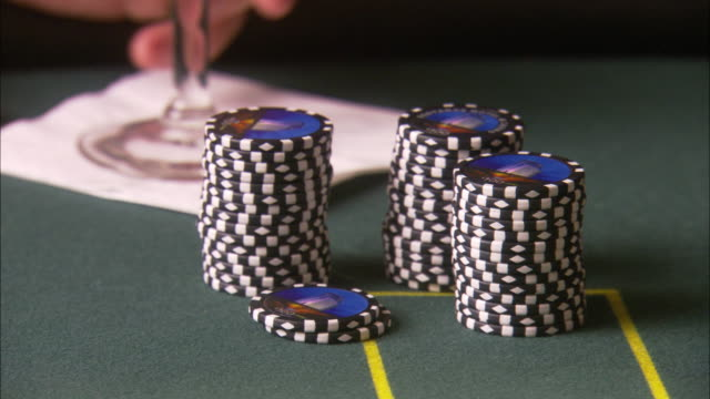 close angle of a stack of chips on a green felt gambling table.  a man's hands behind the chips as the dealer puts down the cards for blackjack. - hand of cards stock videos & royalty-free footage