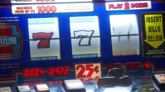 close angle of a slot machine in a casino.  a man opens the machine, closes it, and the machine comes up a winner with all sevens.  winning, gambling. - spielautomat stock-videos und b-roll-filmmaterial