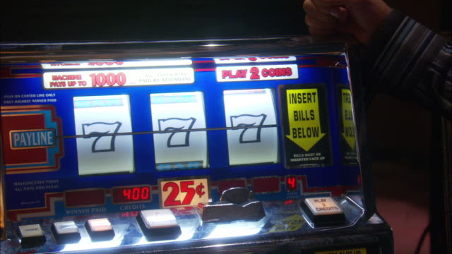 close angle of a slot machine in a casino.  a man opens the machine, closes it, and the machine comes up a winner with all sevens.  winning, gambling. - man and machine stock videos & royalty-free footage