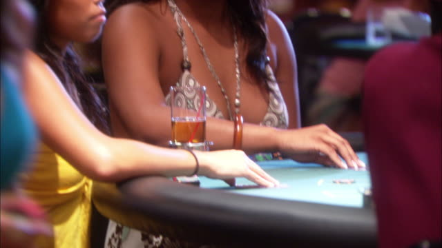 pan up from women at gambling table playing blackjack to pit boss shouting orders. pans left to dealers encouraging unseen gamblers. casinos. - blackjack stock videos and b-roll footage