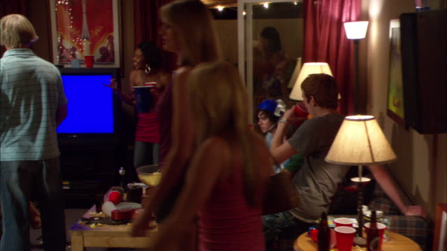 medium angle of house party. young men and women stand around living room talking and holding plastic cups. pov pans through room. - party stock-videos und b-roll-filmmaterial