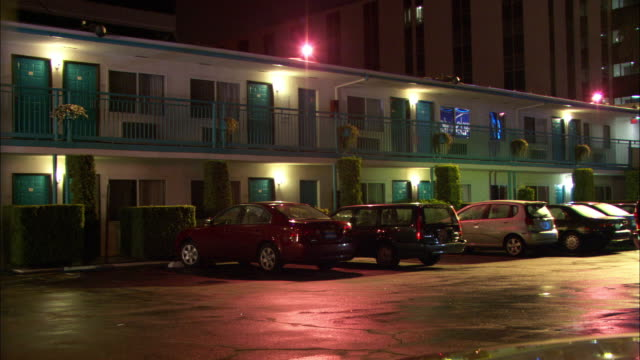 wide angle of two story motel or hotel in middle of city. cars are parked in motel parking lot directly outside of rooms. room front doors and windows are visible. tall office building in bg. - motel stock videos and b-roll footage