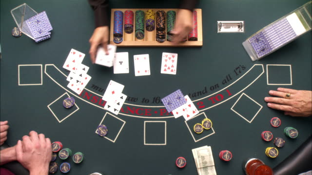 wide angle overhead of game of casino blackjack. dealer takes bets and deals cards. four sets of hands play at table. gambling. - blackjack video stock e b–roll