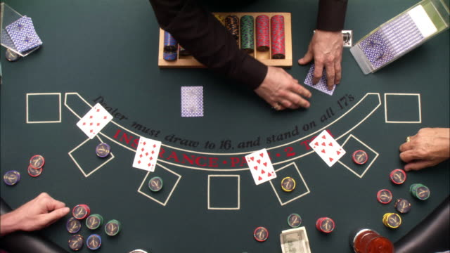 wide angle overhead of game of casino blackjack. dealer takes bets and deals cards. four sets of hands play at table. gambling. - blackjack stock videos and b-roll footage