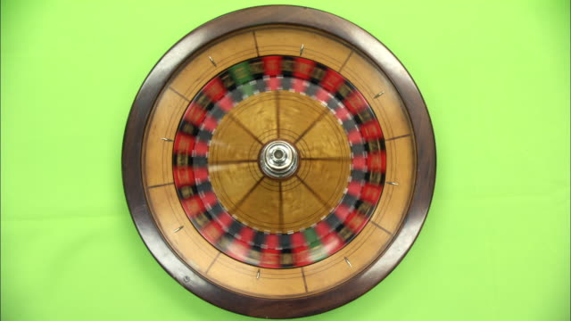 close angle overhead of a spinning roulette wheel on a green matte background. ball rolls around wheel, then stops before wheel stops. gambling casinos, visual effects, compositing. - roulette stock videos & royalty-free footage