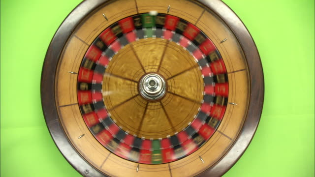 close angle overhead of a spinning roulette wheel on a green matte background. ball rolls around wheel, then stops before wheel stops. gambling casinos, visual effects, compositing. - roulette wheel stock videos and b-roll footage