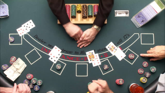 high angle down, birdseye pov of game of casino blackjack. dealer takes bets and deals cards. four sets of hands play at table. gambling. camera zooms in and out on action. fast motion. - blackjack stock videos and b-roll footage