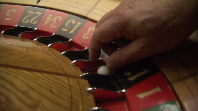 close angle of spinning roulette wheel. ball rolls around and comes to a stop. a man's hand stops the wheel, spins the wheel again and tosses ball. repeats several times. gambling. casinos. - roulette stock videos and b-roll footage