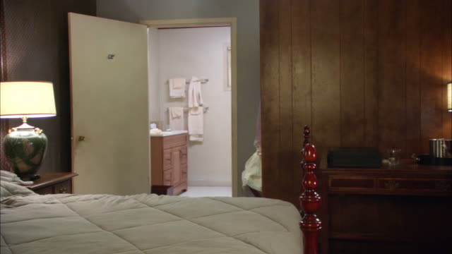 vidéos et rushes de medium angle of low class or cheap hotel or motel room. wood paneling, bed in foreground with wooden frame. open bathroom door. - domestic room