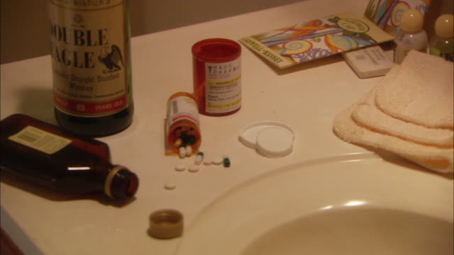 CLOSE ANGLE HANDHELD OF AN APPARENT SUICIDE SCENE. PILLS FROM OPEN BOTTLES STREWN ON SINK ALONG WITH OPEN ALCOHOL BOTTLES.