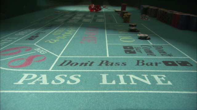 vidéos et rushes de close angle of craps table from low pov. poker chips have been placed on the board for various bets. shooter on opposite end of table rolls oversize dice several times. - casino