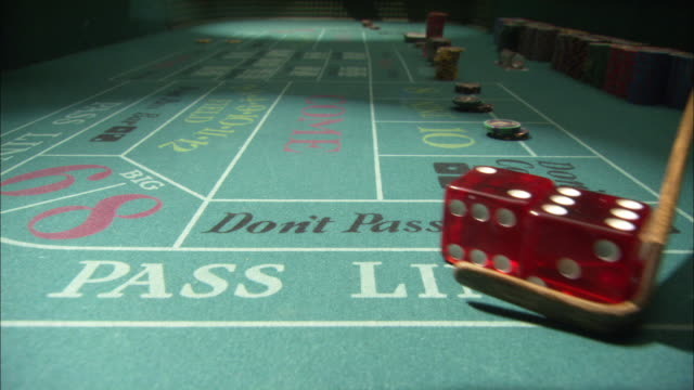 close angle of craps table from low pov. poker chips have been placed on the board for various bets. shooter on opposite end of table rolls oversize dice several times. - casino stock-videos und b-roll-filmmaterial