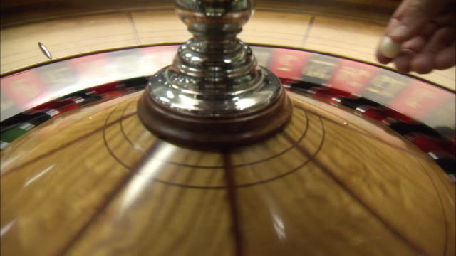 close angle of roulette wheel spinning. hand reaches down to spin wheel and launches ball into wheel. repeat several times. casinos, gambling, games. - roulette wheel stock videos and b-roll footage
