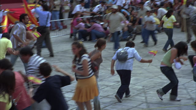 hand held of crowd or gathering of people running inside replica of plaza mayor in salamanca spain. government or municipal building. panic reaction from disaster, emergency, evacuation, or other event. security guards standing by small stage appear confu - evacuation stock videos & royalty-free footage