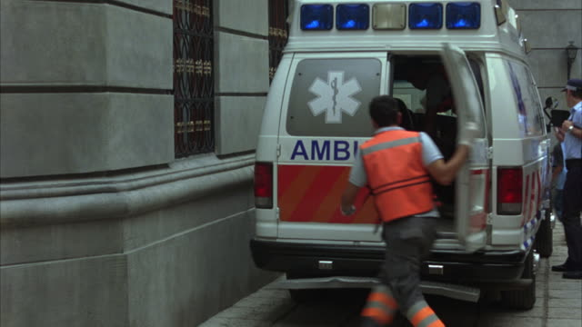 """vídeos y material grabado en eventos de stock de hand held of paramedics and emergency personnel assisting people running through cobblestone side street in europe. paramedics close back door of """"ambulancia"""" ambulance. people have blood on clothing. panic reaction to disaster, evacuation, or emergency s - ambulancia"""