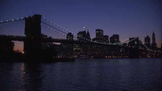 wide angle of the brooklyn bridge. lights line the bridge's suspension cables. pov pans from brooklyn's rocky shoreline to the bridge. new york city skyline visible in bg. matching dx/nx 4062-001 to 4062-018. - wide stock videos and b-roll footage