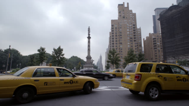 wide angle of columbus circle monuments, fountain, and traffic circle. apartment buildings visible in background. park, plaza, or courtyard. pedestrians walk past on sidewalk. - columbus circle stock videos & royalty-free footage