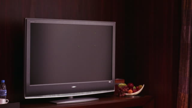 wide angle of television screen in bedroom or hotel room with fruit bowl. - bedroom stock videos & royalty-free footage