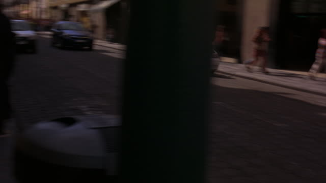 hand held of panicked crowd of people running on sidewalk guided by police officer.  chevrolet astra car chasing police car with flashing lights or bizbar swerving on cobblestone street in city. near collision or car crash.  could be europe or mexico city - 2008 stock videos and b-roll footage