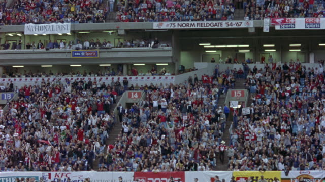 WIDE ANGLE OF CROWD, SPECTATORS IN SPORTS ARENA OR FOOTBALL STADIUM, CHEERING, WATCHING SPORTS.