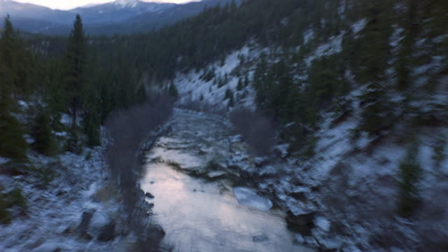 aerial of river in between snowy mountains. see pine trees along mountain side and river bank. see trees without leaves alongside pine trees. see rocks in river and near river bank. - north america stock videos & royalty-free footage