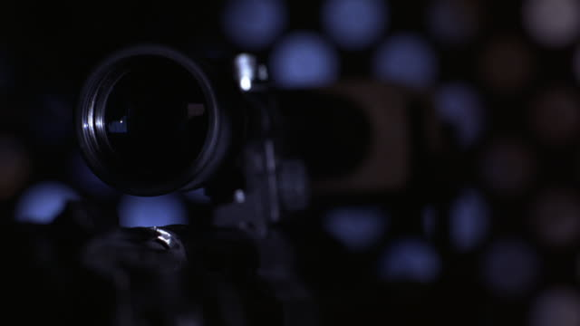 vídeos de stock, filmes e b-roll de close angle of scope mounted on top of assault rifle. gun moves automatically, tracking subject. daytime sky behind grate-like wall in bg. could be gunman, assassin, sniper, soldier or spy. - sony pictures entertainment