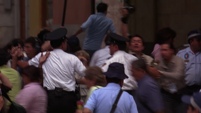 hand held of police officers directing panicked crowd of people running to safety from landmark plaza mayor. reporters, photographers and news crew with boom mic and cameras. could be emergency, evacuation or disaster. europe or mexico city. - angst stock-videos und b-roll-filmmaterial