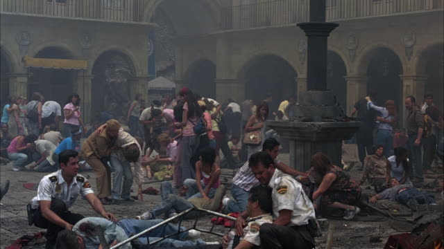 wide angle of people  injured and dead bodies from explosion or accident in plaza or courtyard. police officers or paramedics help. europe. smoke and debris visible. - courtyard stock videos & royalty-free footage