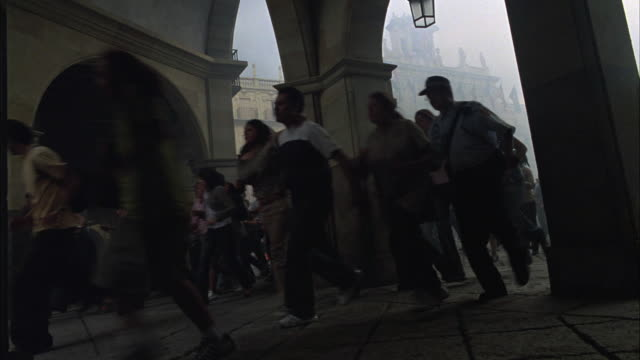 wide angle, tilted angle of crowd of people running or fleeing out of plaza mayor. smoke from accident, explosion, or fire fills air. panic reaction. - crowd running scared stock videos & royalty-free footage