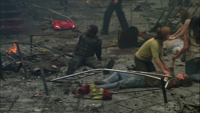 WIDE ANGLE OF INJURED AND DEAD PEOPLE OR CIVILIANS FROM ACCIDENT, FIRE, OR EXPLOSION. POLICE OFFICERS HELP. TWO WOMEN SEEK HELP FOR MAN LYING ON GROUND. SMOKE AND DEBRIS VISIBLE.